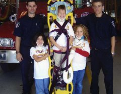 2 fire fighters standing in front of fire truck with 3 children who are wearing medical assistive devices