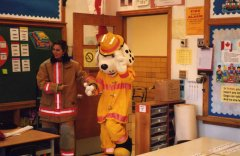 Person dressed in Sparkey the dog costume with a fire fighter in a classroom